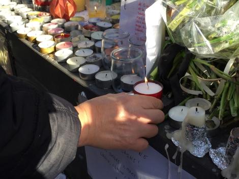 A woman places a candle at the memorial at Place de la Republique. ©Lisa Anselmo