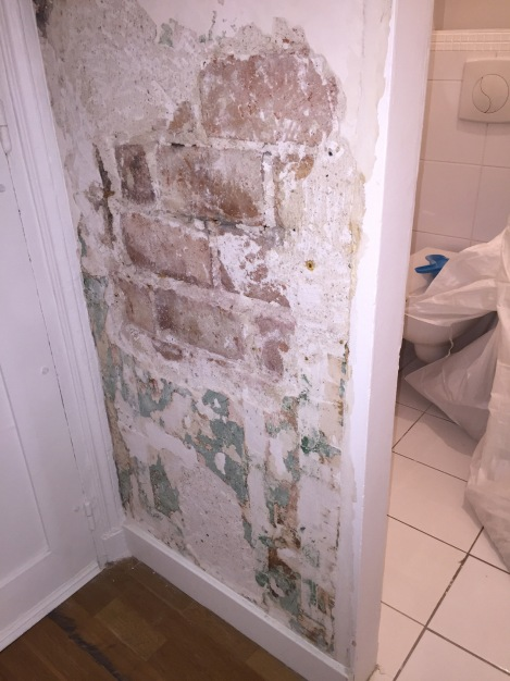 Walls being scraped to the brick, to allow them to dry out.