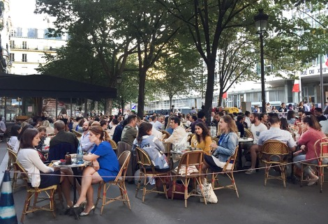 A crowd of people sitting on a plaza in Paris.