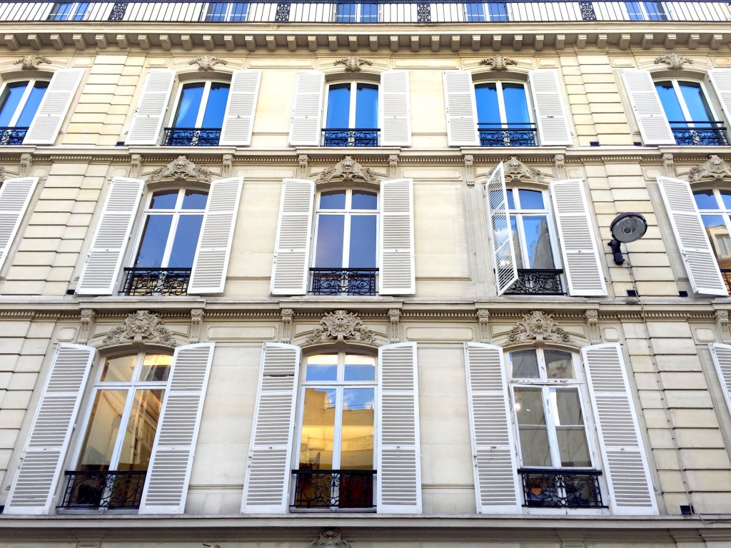 Facade of a Paris apartment building with white shutters