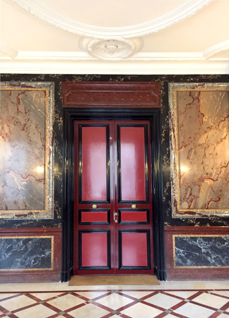 Lobby of a building in Paris, red door with colorful marble walls