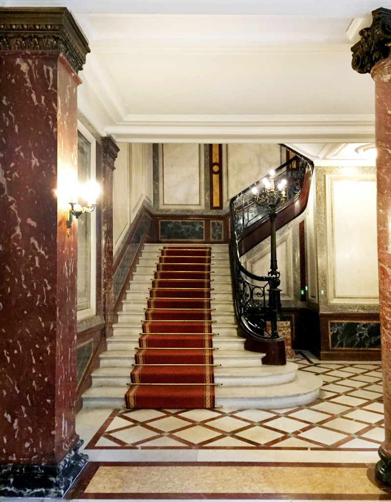 Marble lobby of a building in Paris with sweeping staircase